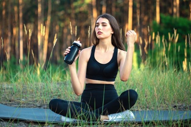 Atleta ragazza con si siede nel parco con una bottiglia d'acqua