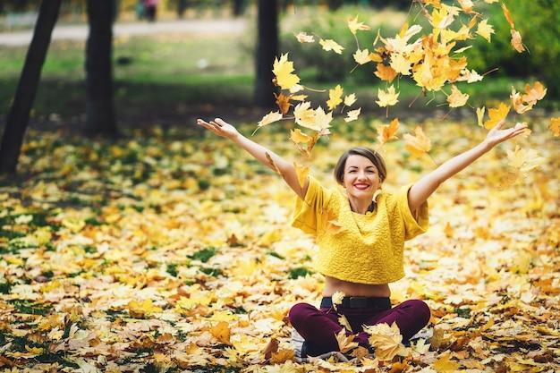 La ragazza in autunno si siede sull'erba e solleva allegramente le foglie gialle. stile di vita.