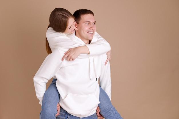 Ragazza sulla schiena di un ragazzo in studio su un marrone