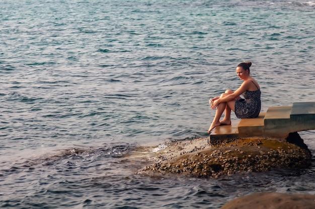Ragazza sullo sfondo del mare tropicale al tramonto. la donna in abiti estivi è seduta sul molo. mi mancano i viaggi. viaggi. sogno femminile. stile di vita estivo, sulla spiaggia con palme e mare sullo sfondo