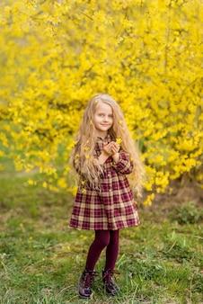 Ragazza su uno sfondo di fiori gialli. un bambino in un giardino fiorito primaverile