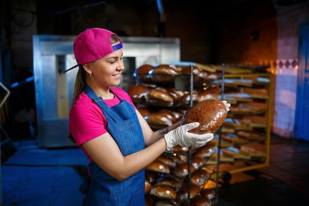 Ragazza fornaio lavora in una panetteria. primo piano di pane fresco croccante