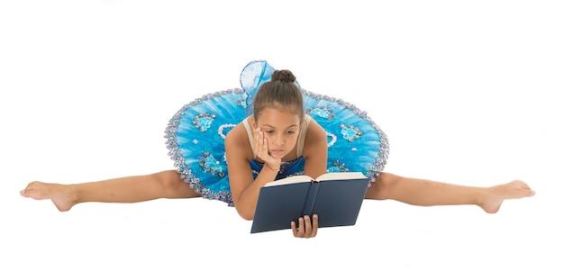 La ballerina della ragazza che allunga spacca mentre legge il libro. problemi di carriera nel balletto. privare i bambini ballerina. la maggior parte del tempo il ballerino bambino trascorre l'allenamento in palestra praticando lo stretching. non c'è tempo per studiare a scuola.