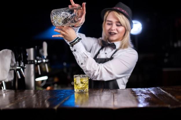 Il barista della ragazza formula un cocktail sulla birreria