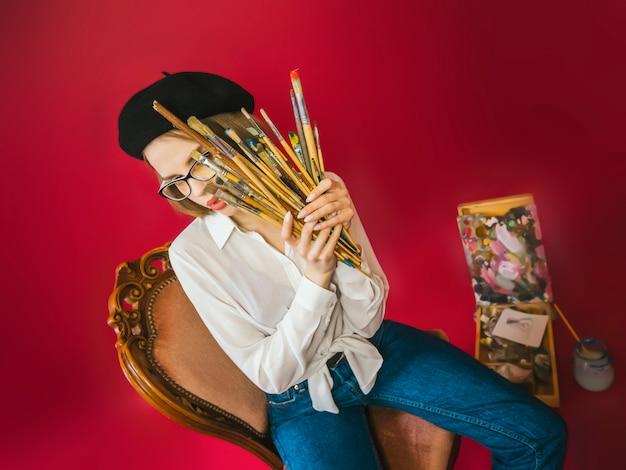 Ragazza in basco basco berretto su sedia vintage in occhiali da lettura e camicetta bianca con spazzole e cavalletto. concetto di artista pittore di moda.