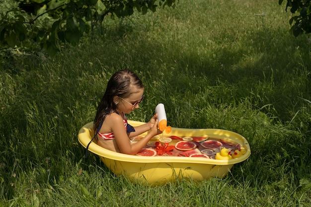 Una ragazza fa il bagno in una vasca da bagno con anatroccoli giocattolo e versa il gel doccia in acqua con frutta e un giglio