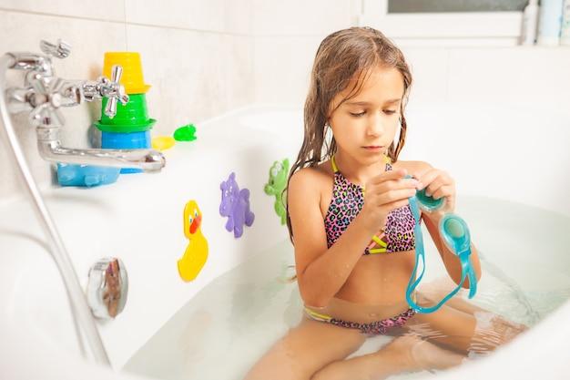 Una ragazza in bagno indossa occhiali da nuoto