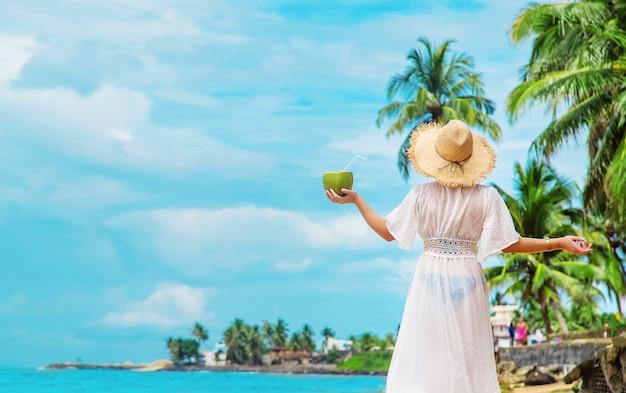 La ragazza sulla spiaggia beve la noce di cocco. messa a fuoco selettiva. natura.