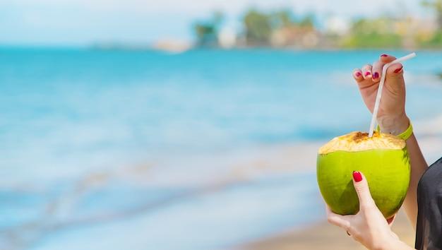 La ragazza sulla spiaggia beve la noce di cocco.