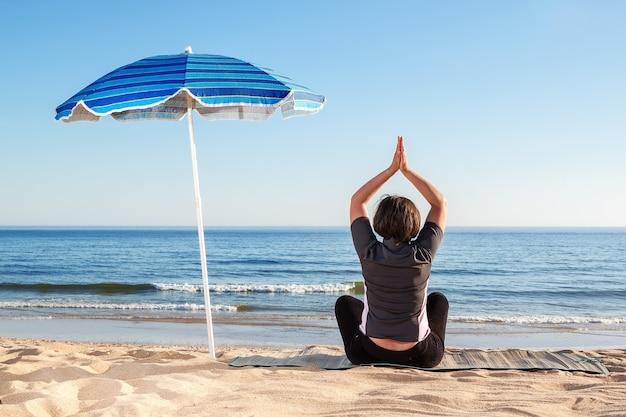 Una ragazza sulla spiaggia pratica lezioni di yoga. estate sulla sabbia.