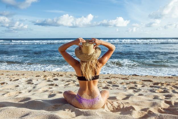 La ragazza sulla spiaggia ha raggiunto la vista posteriore