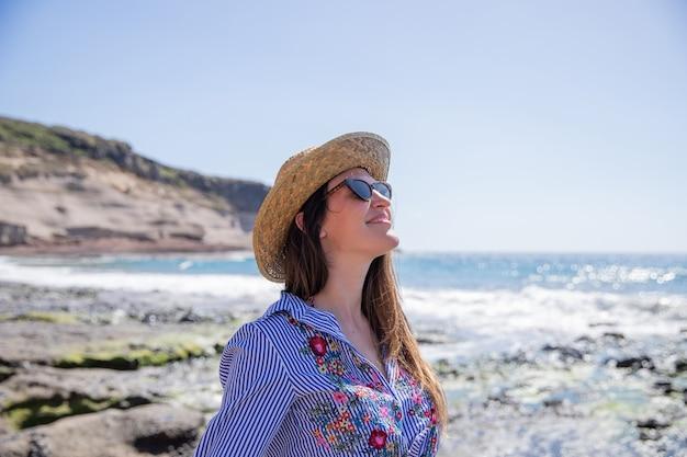 La ragazza in spiaggia si rilassa e si gode le vacanze, indossa occhiali da sole e un cappello estivo.