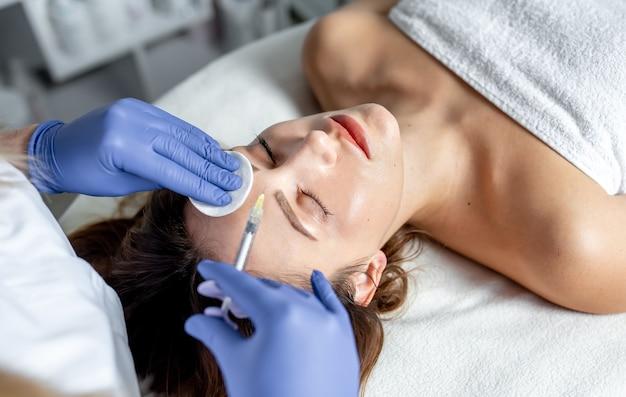 L'estetista della ragazza fa le iniezioni sulle labbra e sul viso di una bella donna in un cuneo cosmetico. concetto di cosmetologia.