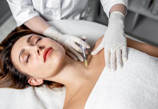 L'estetista della ragazza fa le iniezioni sulle labbra e sul viso di una bella donna in un cuneo cosmetico