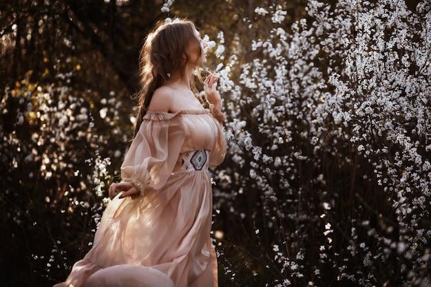 Ragazza in un bellissimo abito arioso in primavera nei colori bianchi. passeggiata nella natura