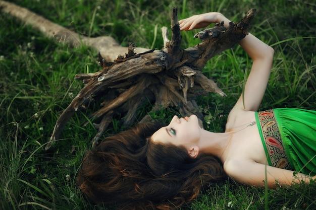 La ragazza in un bellissimo vestito verde giace sull'erba vicino alle radici di un albero e sogna. donna con trucco luminoso in natura, cosmetici naturali