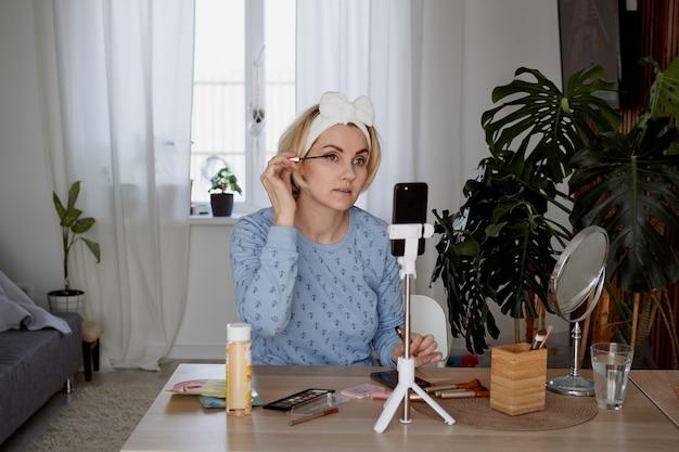 Girl beauty blogger registra podcast per gli abbonati sul trucco blogging, broadcast e concetto di cosmetici