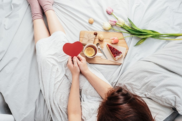 La ragazza a letto la mattina ha ricevuto fiori, regali e colazione a letto. congratulazioni per san valentino.