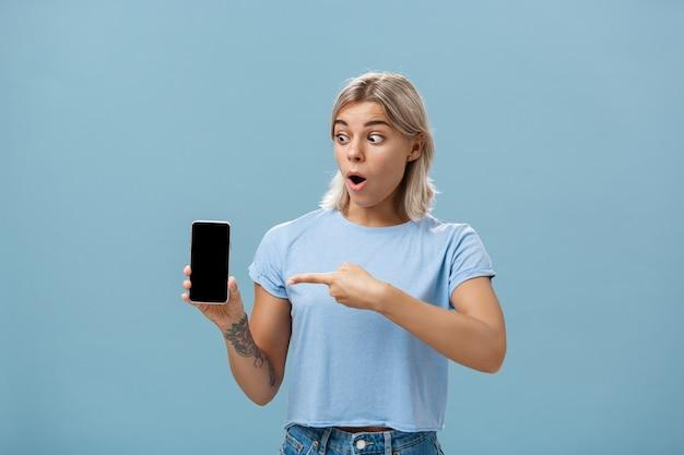 Ragazza stupita con il nuovo smartphone ricevuto il giorno del compleanno.