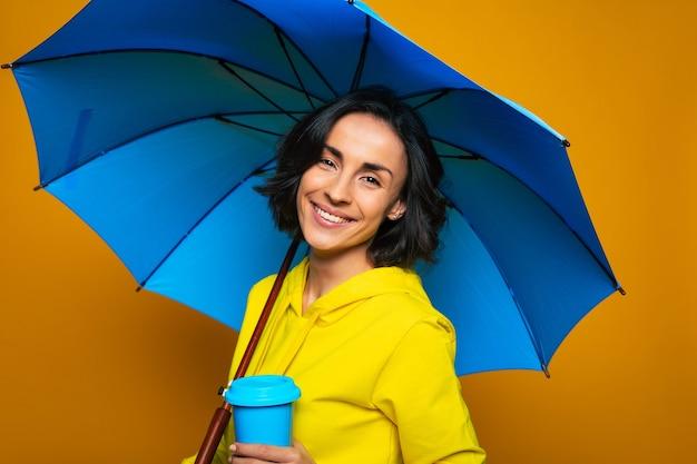 Ragazza che viene toccata, con un sorriso sul viso, in una giacca gialla sotto un ombrello, con una tazza termica blu nella mano sinistra, guardando dritto con gli occhi lucidi.