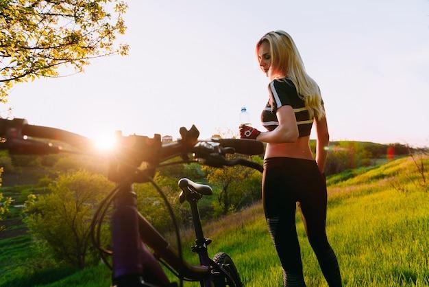 Il ciclista della ragazza beve acqua pulita dopo l'allenamento vicino alla sua bicicletta sotto i raggi del sole nascente