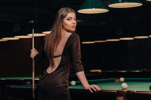 Una ragazza in un club di biliardo con una stecca in mano