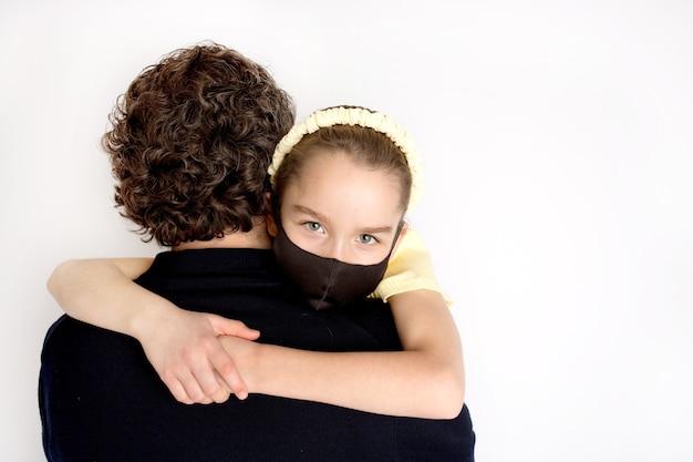 Una ragazza con una maschera antibatterica nera e una maglietta gialla tra le braccia di suo padre. la figlia abbraccia forte suo padre. concetto di famiglia, amore e cura.