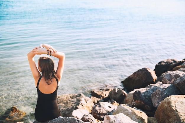 Ragazza in abito nero sullo sfondo del mare o del lago donna rilassata sul mare sulla grande spiaggia di pietra selvaggia