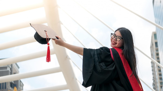 Ragazza in abiti neri e tenere il certificato di diploma sorridente con felice laureato.