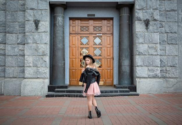 Ragazza con cappello nero in posa sulla strada nella città vecchia