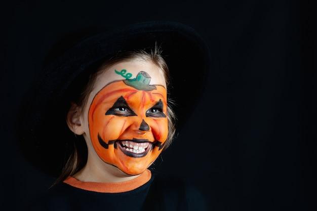 La ragazza con un cappello nero e il trucco di zucca per halloween guarda lateralmente, imita.