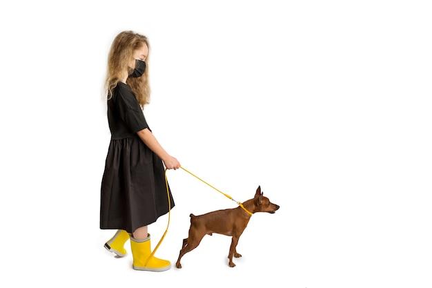Una ragazza con una maschera antivirale protettiva nera porta a spasso il cane. nuova realtà della vita durante la pandemia di covid-19. precauzioni per la pandemia di coronavirus. viaggiare con animali domestici. foto di alta qualità