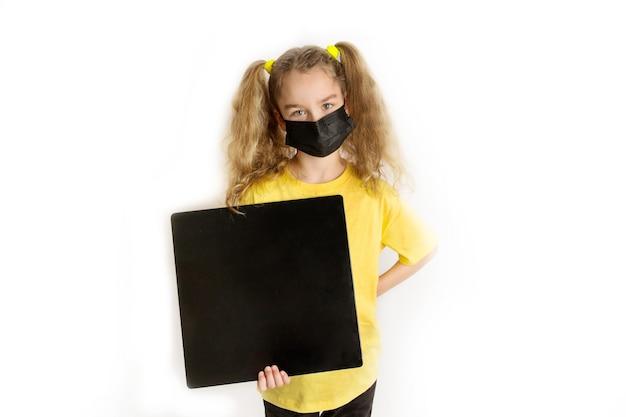 Una ragazza con una maschera medica protettiva nera e una maglietta gialla tiene un quadrato nero per l'iscrizione. sfondo bianco. fotografia in studio. foto di alta qualità