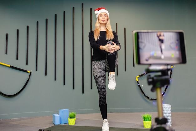 Una ragazza in abiti sportivi neri e cappello da babbo natale fa fitness e si registra sulla telecamera.