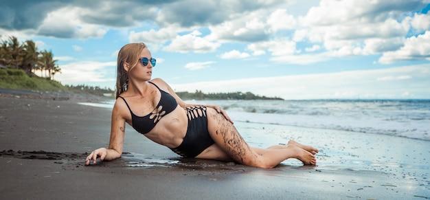 Ragazza in costume da bagno nero e occhiali da sole è sdraiata sulla spiaggia con panorama di banner di sabbia nera