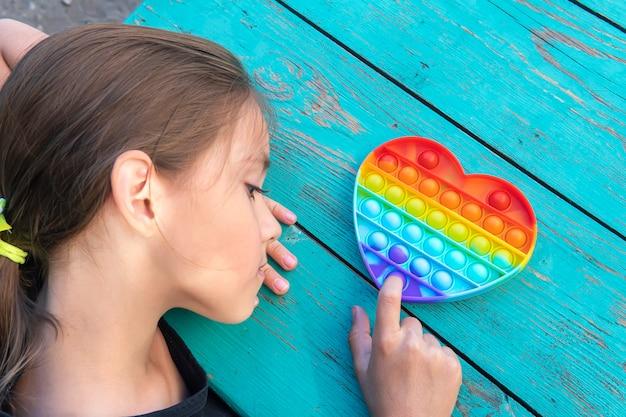 Una ragazza con una maglietta nera gioca con un giocattolo alla moda. colorato giocattolo sensoriale antistress fidget push pop nelle mani dei bambini, può essere utilizzato per l'allenamento con persone autistiche