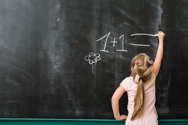 Ragazza a lavagna in classe di matematica