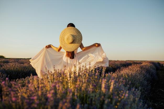Ragazza in campo di lavanda in fiore.