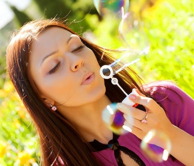 La ragazza soffia la bolla di sapone contro un'erba di sfondo