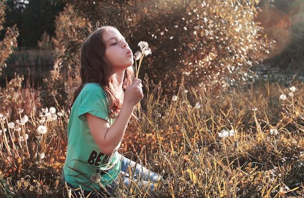 Ragazza che soffia i semi da un fiore di dente di leone nel pomeriggio autunnale