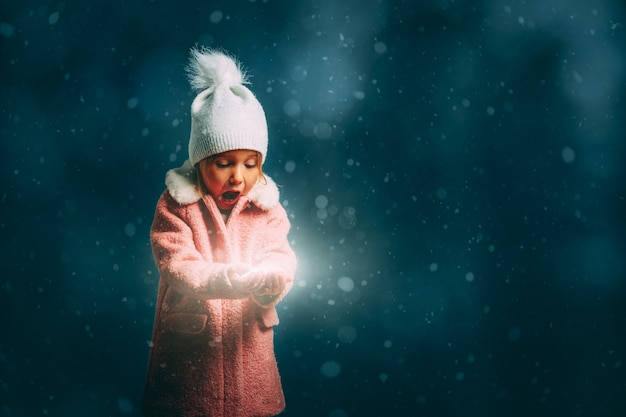 Ragazza che soffia nella neve su uno sfondo nero alla vigilia di natale