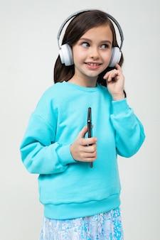 La ragazza in una camicetta blu si rilassa con la musica in grandi cuffie alla moda.