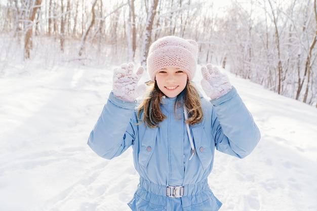Una ragazza con un cappotto blu e un cappello rosa mostra la neve che si attacca ai guanti rosa dopo aver giocato a palle di neve. passeggiate invernali e giochi con i bambini. vestiti per il gelo.