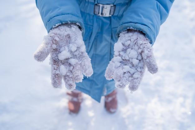 Una ragazza con un cappotto blu mostra la neve che si attacca ai guanti rosa dopo aver giocato a palle di neve. passeggiate invernali e giochi con i bambini. vestiti per il gelo.