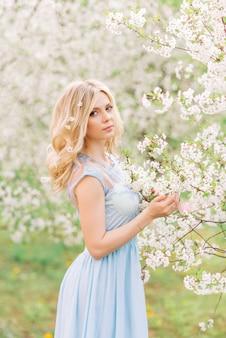 Ragazza in un giardino blu del vestito in primavera. su uno sfondo di fiori bianchi
