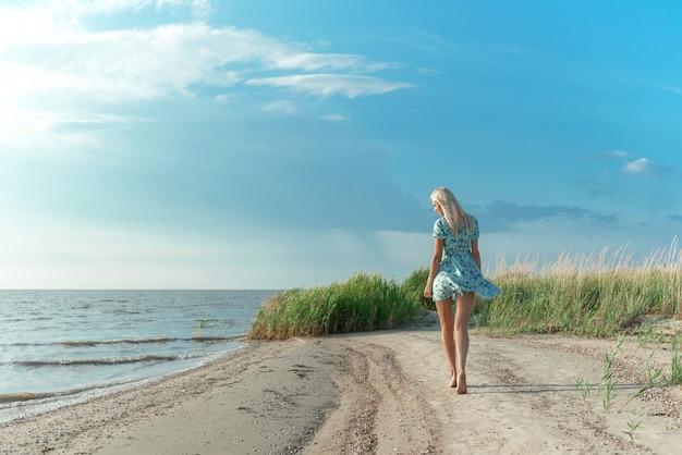 Una ragazza in abito blu passeggia lungo la riva del mare