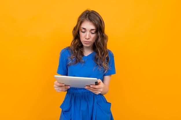 Ragazza in un vestito blu con un tablet nelle sue mani su uno sfondo giallo e arancio con spazio di copia