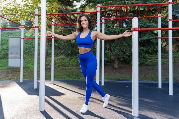 Ragazza in abiti fitness blu lavora sul campo sportivo all'aperto