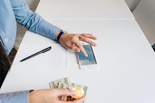 Una ragazza con una camicia blu tiene in mano un bitcoin d'oro, guarda la valuta crittografica della grafica