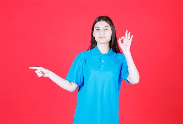 Ragazza in camicia blu in piedi su sfondo rosso che indica il lato sinistro